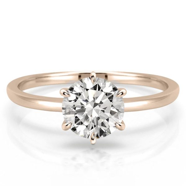 delicate round cut engagement ring with claw prongs in rose gold