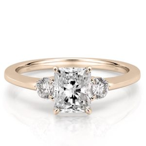 radiant engagement ring with three stones and claw prongs in rose gold