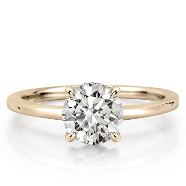 round cut engagement ring with claw prongs and hidden halo in yellow gold
