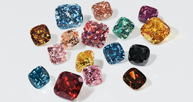 different colored diamonds in cushion cut shape on white surface