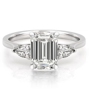 engagement ring with emerald cut center stone and pear side stones in white gold