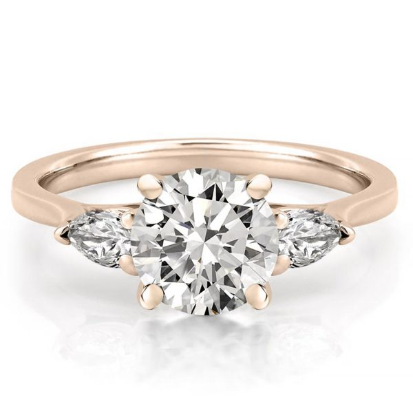 engagement ring with round center stone and pear side stones in rose gold
