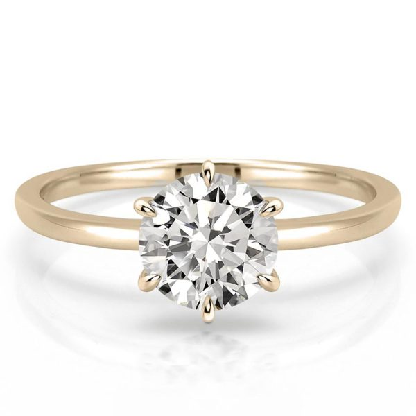 delicate round moissanite engagement ring with claw prongs in yellow gold