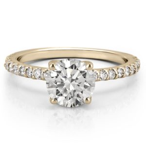 round cut affordable moissanite engagement ring with diamonds on band and basket in yellow gold